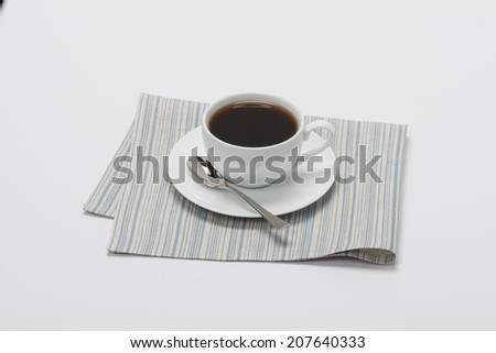 Black Coffee In White Cup On Folded Natural Linen Napkin. White Background.