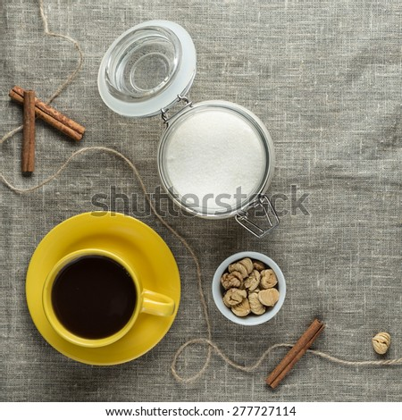 Black coffee in yellow cup with sugar and cinnamon sticks on grey fabric background - stock photo
