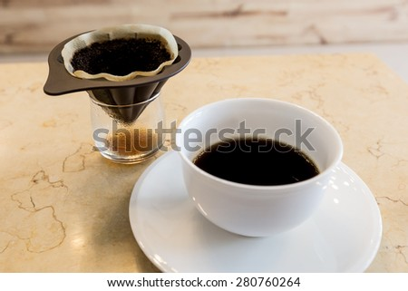 black coffee on white mug with coffee ground - stock photo