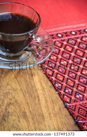black coffee on wooden table with handmade red tablecloth Thai style