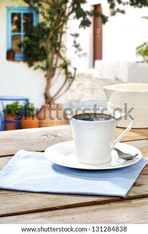 black coffee served on an aged table in a yard of a Greek island - stock photo