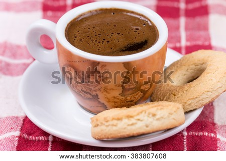Black coffee with round tea cookies on the plate.