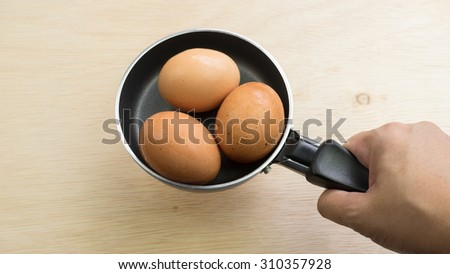 Black color metal mini frying pan and few chicken eggs on wooden table surface. Concept of breakfast cooking utensil. Slightly de-focused and close-up shot. Copy space.