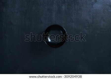 Black color wooden table top view. On the table are the Japanese wooden bowl. - stock photo