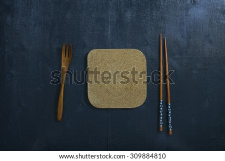Black color wooden table top view. On the table are the Japanese wooden spoon, chopsticks. - stock photo