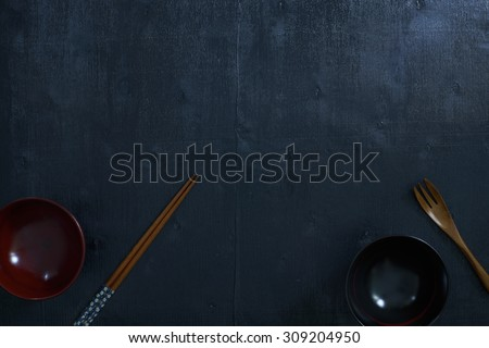 Black color wooden table top view. On the table are the Japanese wooden spoon, chopsticks, bowl. - stock photo