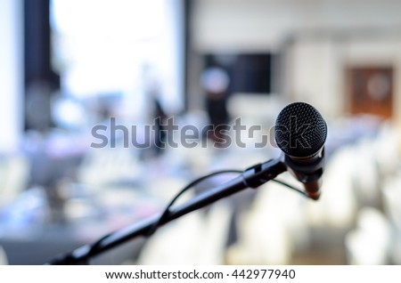 Black colored microphone isolated at an event. Bokeh background with copy space available.