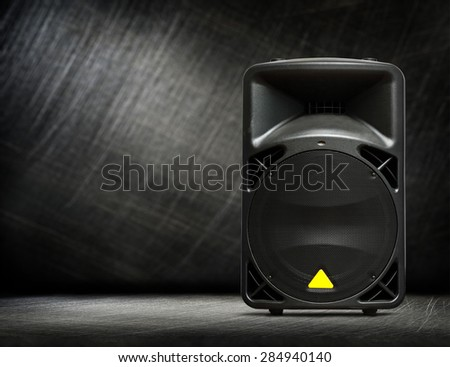 Black column speaker on steel scratchy background - stock photo
