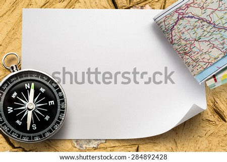 Black compass and map on blank paper - stock photo