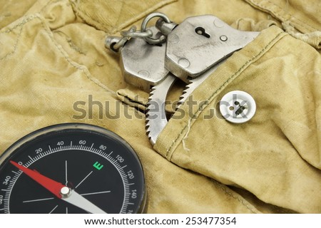 Black Compass and Shabby Handcuffs On The Weathered Backpack - stock photo