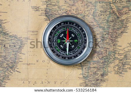 Black compass on old vintage map, Atlantic, macro background