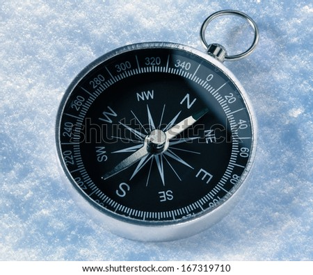 Black compass on snow background