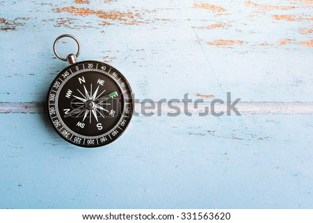 Black compass on wooden board - stock photo