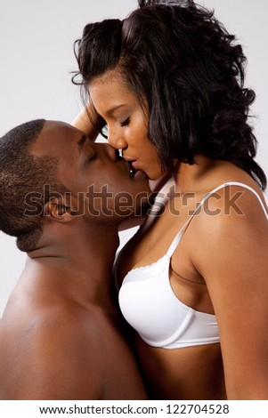 Black couple in romantic foreplay, she is wearing only bra and sitting in his lap while he kisses her affectionately - stock photo