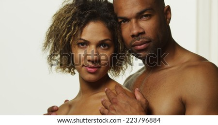 Black couple standing and looking at camera