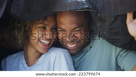 Black couple standing under coat trying not to get wet - stock photo