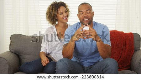 Black couple texting on smartphone - stock photo