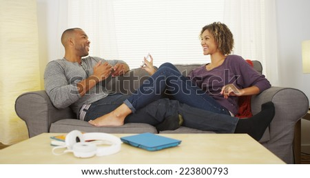 Black couple using electronic devices on couch