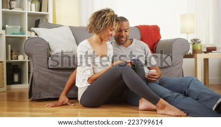 Black couple using smartphones on floor - stock photo