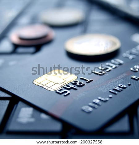 Black credit card on computer keypad with money coins - stock photo