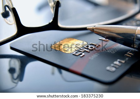 Black credit card with glasses and ballpoint - stock photo
