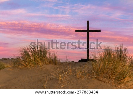 Black cross on  a sand dune hill with a colorful morning sky. - stock photo