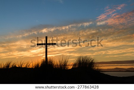 Black cross on  a sand dune hill with a morning sky.