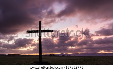 Black cross with a clouded morning sky.