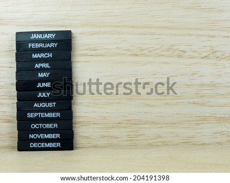 Black cubes, 12 months arranged on stack on wooden background