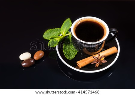 Black Cup and Saucer with Strong Black Coffee Served with Fresh Spices - Mint Sprig, Cinnamon Stick and Star Anise - and Trio of Chocolate Covered Coffee Beans on Shiny Black Surface with Copy Space - stock photo