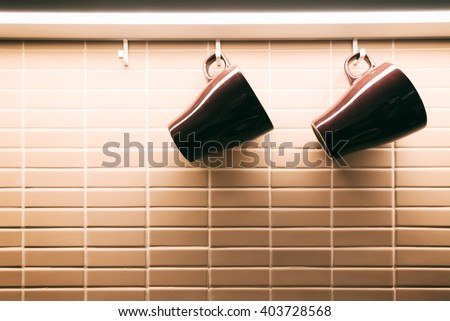 Black cups hanging on wall. - stock photo