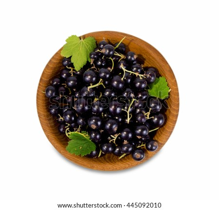 black currant in a wooden bowl. Top view. Ripe and tasty currant isolated on white background. - stock photo