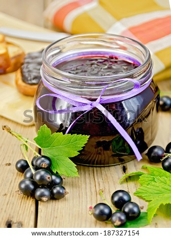 Black currant jam in a glass jar, fresh blackcurrant with leaves, napkin on a wooden board - stock photo