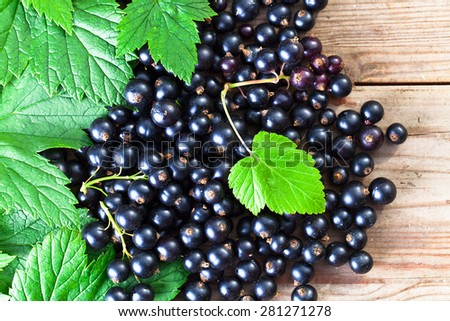 black currant, ripe berries and green leaves on  wooden table - stock photo