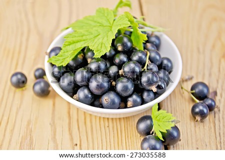 Black currants in a white bowl with green leaves on a wooden boards background - stock photo