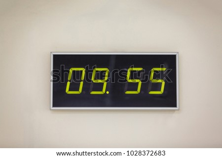 Black digital clock on a white background showing time 9 hours 55 minutes