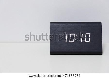 Black digital clock on a white background showing time 10:10 (ten hours ten minutes)