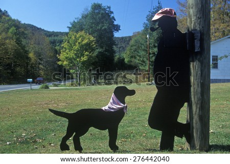 Black dog and man smoking pipe wooden cutouts by roadside, Route 39, WV