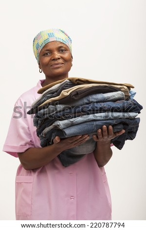 Black domestic worker holding laundry - stock photo