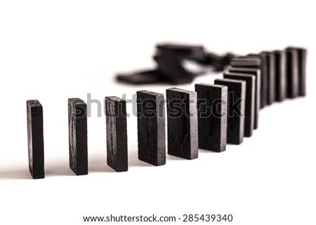 Black dominoes in a curved line ready to topple, on a white background - stock photo