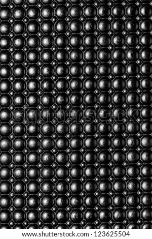 Black dotted plastic surface texture background.