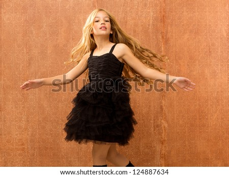 black dress kid girl dancing and twisting on vintage background - stock photo