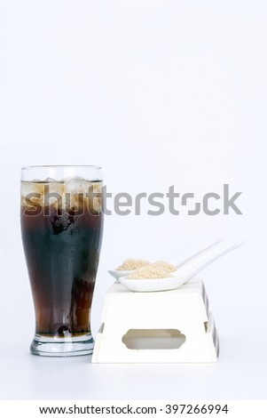 black drink (cola) and sugar over lettuce over white background