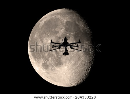 Black drone on the night sky in front of the moon - stock photo