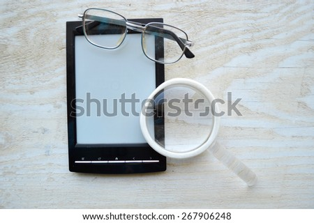 black e-book,reading glasses,Notepad,diary,reading glasses and magnifying glass on wooden table - stock photo