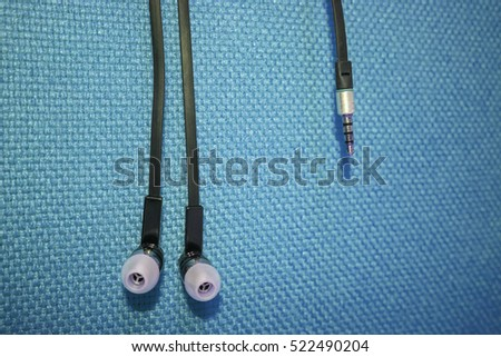 Black Earphone or earphones on Blue background the Black earphones for using digital music or smart phone | earbuds isolated | Music Technology