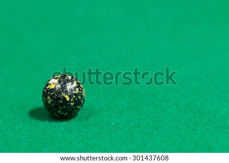 Black Egg like Colorful Marble Balls on Green background - stock photo