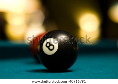 Black eight billiard ball on a pool table