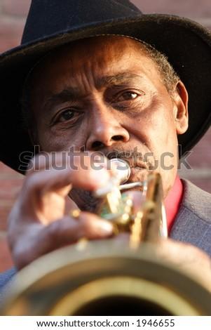 Black elderly man playing an old trumpet. - stock photo