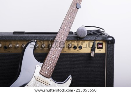 Black electric guitar, amp and mic on white background - stock photo